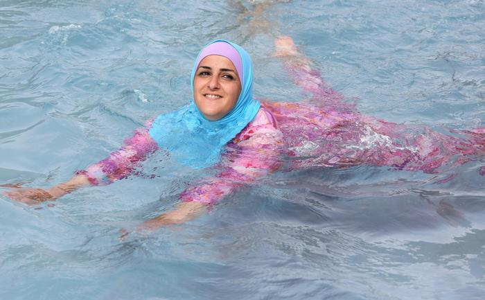 A young Turkish woman cools off while wearing a burkini at an open-air bath in Berlin, Germany, 20 August 2012.  ANSA/STEPHANIE PILICK