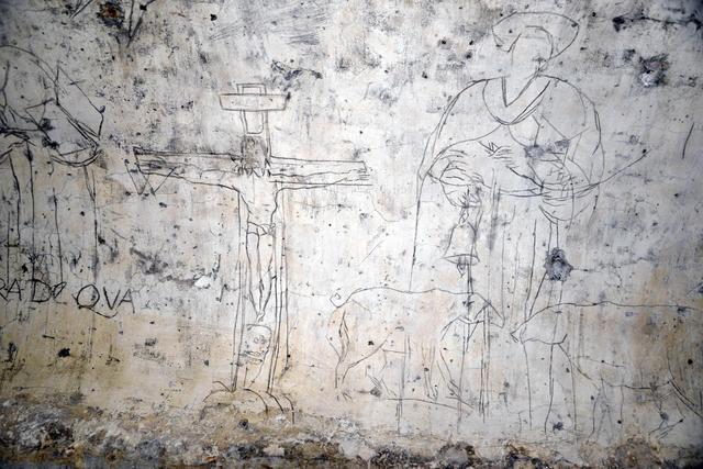 Nella foto: sulla parete opposta alla Vergine, un Cristo crocefisso e a lato San Rocco, che regge una campanella attorniato da due maialini: il Perucolo si era servito di un chiodo o punzone per incidere le figure su uno strato di calce fresca, per poi ripassare sui segni un pennellino imbevuto di acqua mista a polvere di carbone. ANSA/ANDREA MEROLA