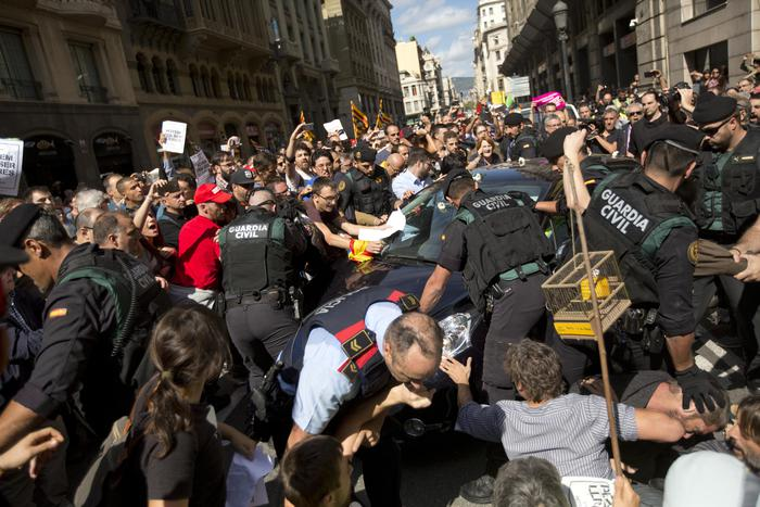 Demonstrators try to stop the car carrying Xavier Puig, a senior at the Department of External Affairs, Institutional Relations and Transparency of the Catalan Government office, after he was arrested by Guardia Civil officers in Barcelona, Spain, Wednesday, Sept. 20, 2017. Spanish police arrested 12 people Wednesday in raids on offices of the regional government of Catalonia, news reports said, intensifying a crackdown on the region's preparations for a secession vote that Spain says is illegal. (ANSA/AP Photo/Emilio Morenatti) [CopyrightNotice: Emilio Morenatti]