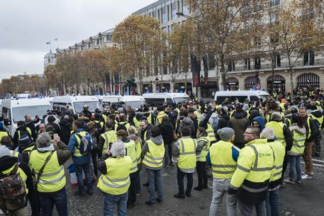 Protestors wearing yellow jackets face riot police officers on the Champs-Elysees avenue in Paris, Saturday, Nov.24, 2018. France is deploying thousands of police to try to contain nationwide protests and road blockades by drivers angry over rising fuel taxes and Emmanuel Macron's presidency. (ANSA/AP Photo/Kamil Zihnioglu) [CopyrightNotice: Jean-Francois BADIAS]